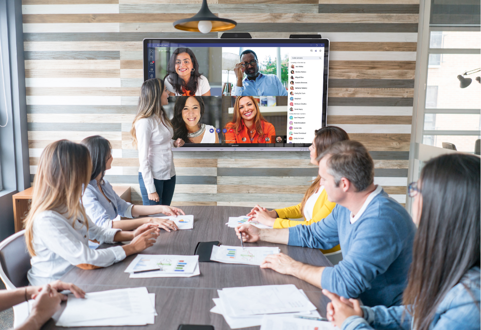 Windows Collaboration Display being used in meeting with 4 video chat participants on screen